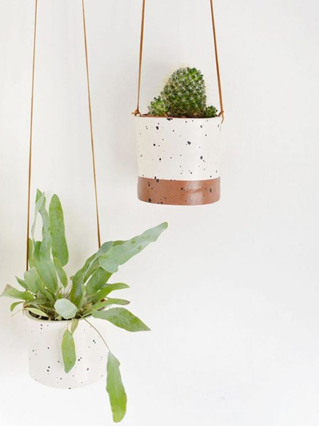 For plants that require little or hardly any water, like cactii or air plants, you can consider using air-dry clay to craft your own unique pots for plant hangers.