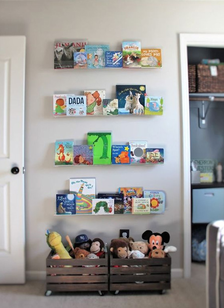 Acrylic or plexiglass storage boxes secured onto the wall with double-sided table make a pretty display for a child's bedroom. Arrange books according to age, so that books for reading now are at the bottom and can be easily rotated as your child grows.