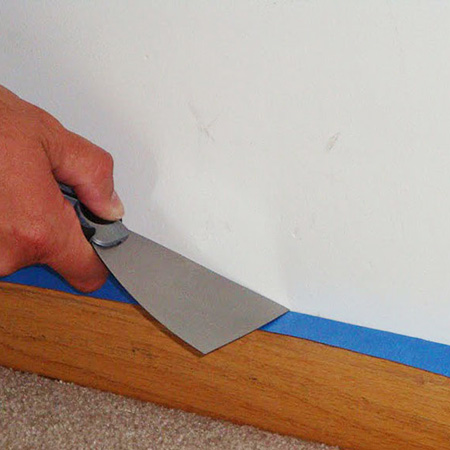 Apply painter's tape over the edge of skirting boards before painting. Run a putty knife over the top to press down the tape for a good seal and to stop any paint bleeds. Use painter's tape instead of masking tape, as the latter tends to leave a sticky residue that's hard to clean and can lift - letting paint run underneath it.