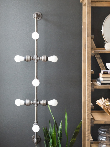 This cool, vertical wall-mounted galvanised pipe light fitting is a simple design that started off as a coat rack and evolved into a light fitting