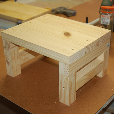 7. Turn the stool over to drive 60mm screws through the top into the leg assembly on both sides.