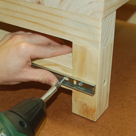 11. Place the small step stool underneath the large step stool and pull out the runners to be able to secure to the leg rail of the small stool. Drive in two screws at the front end of the runner.