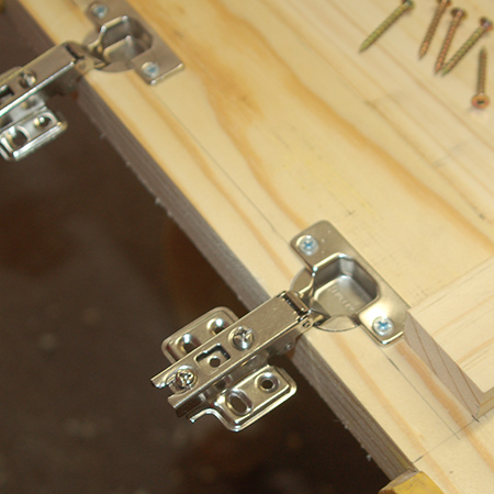 14. Secure the concealed hinges onto the top using 16mm screws.