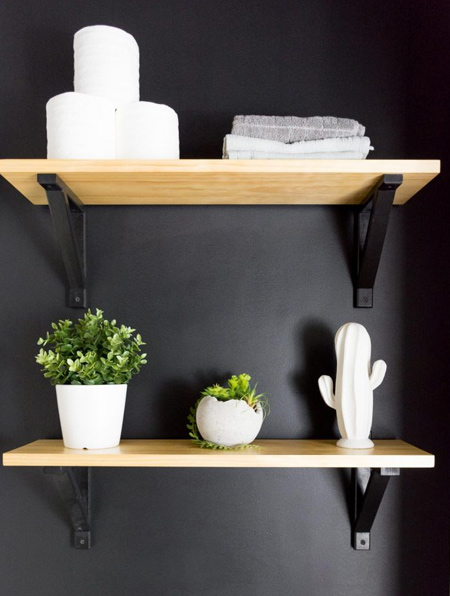 Simple pine shelves steal the show when mounted on a flat black wall.