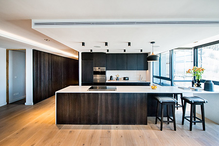 HOME-DZINE | Interior Design - In the kitchen zone, an island clad in natural oak with a polished marble countertop takes centre stage, with white cupboards and classic beaded wall panelling giving the space a light and airy feel.