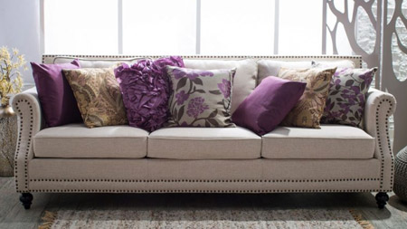 Add visual interest to a netural sofa by layering colour, texture and pattern.