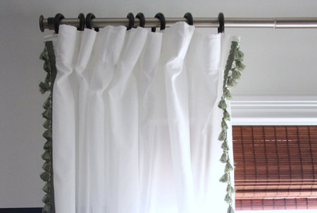 A layered window treatment consisting of bamboo Roman blind and white drapes
