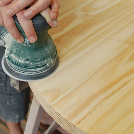 5. Sand the top of the table smooth. It's not always guaranteed that the boards will be one hundred percent level, so start with 120-grit to remove uneven edges and then sand smooth with 180-grit.