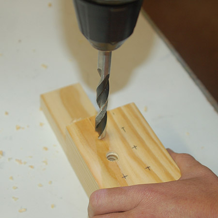 5. Drill 10mm holes through the two block. Place a scrap piece underneath to protect your work surface.