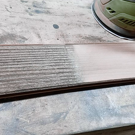 Using 120-grit sandpaper to achieve a reasonably smooth finish, and from there you can leave as is for a rustic table, or sand further with 180- or 240-grit sandpaper.