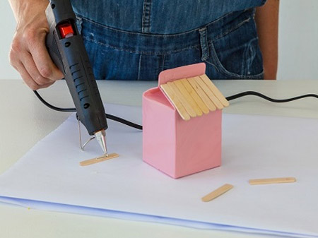 HOME-DZINE | Craft Ideas - Heat up the glue gun and apply a bead of glue to the ice cream sticks to make the roof of the bird feeder.