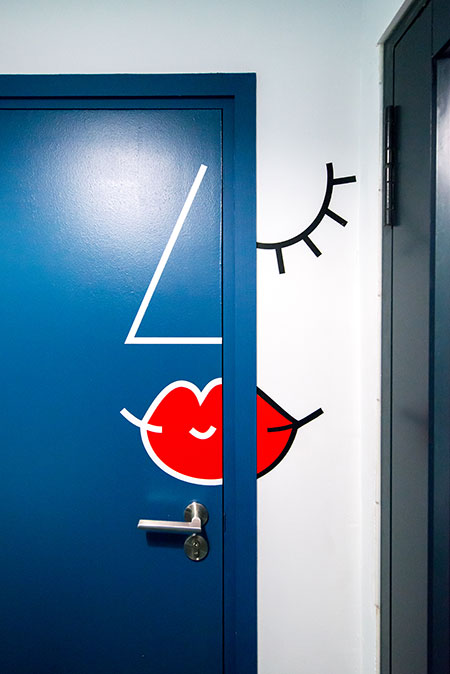 HOME-DZINE | Interior Design - Allport offices - The bathroom area is a particularly creative: the women's restroom door features a Picasso-esque depiction of a feminine face and on the right is a shower room, indicated by a simple shower illustration.
