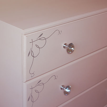 Crystal knobs and hand painted stencil design on drawer fronts.