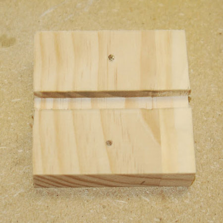 cut two slots in small block of wood