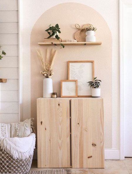 pink wall arch above wood cabinet